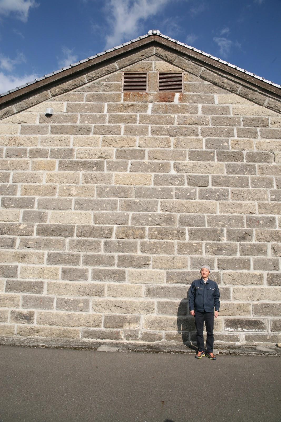 石の外壁と永井さん